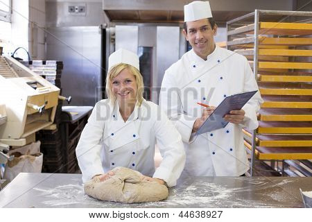 Instructor Instructing An Apprentice In Bakery