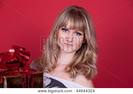 beautiful young blond woman with a gift on a pink background