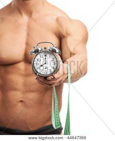Muscular man holding clock and measuring tape