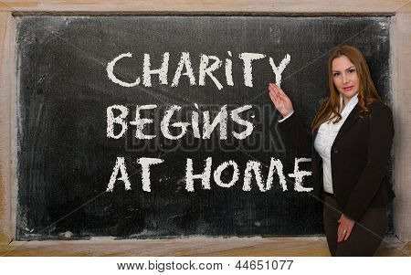 Teacher Showing Charity Begins At Home On Blackboard