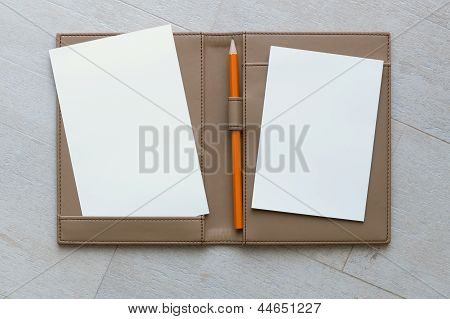Paper And Pencil On Brown Leather Book