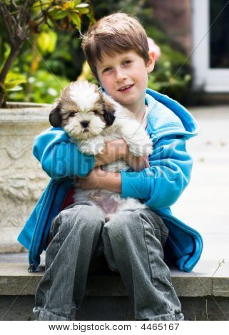 Young Boy Holding A Lhasa Apso Puppy