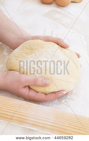 young woman taking the dough with both hands