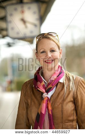 Portrait Of A Beautiful Older Woman Smiling Under Train Station Clock