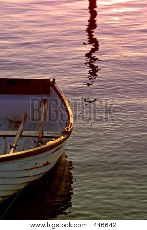 Old Rowing Boat With Oars On Sea During Sunset