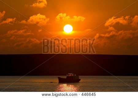 Small Fishing Boat On Its Way Out To Sea At Sunset