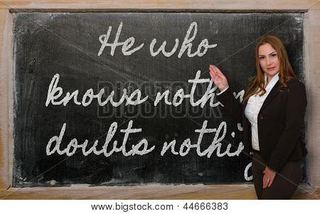 Teacher Showing He Who Knows Nothing, Doubts Nothing On Blackboard