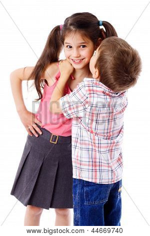 Little boy whispering something to girl