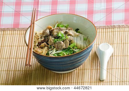 A bowl of Thai style beef noodle with spoon and chopstick.