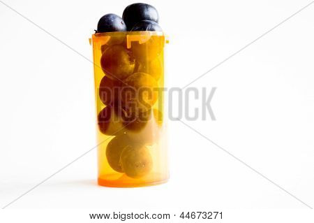 Alternative health concept, pill container filled witih blueberries