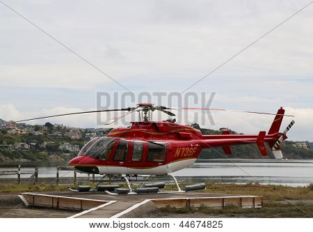 Bell 407 helicopter ready to fly with tourists over  San Francisco Bay