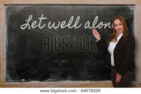 Teacher Showing Let Well Alone On Blackboard
