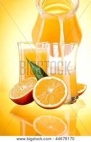 Juice To Pour From Pitcher, Oranges With Leaves On Yellow Background