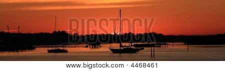 Silhouette Of Sailboats At Sunrise