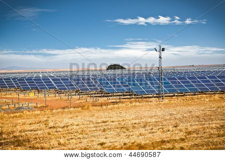 Solar photovoltaics panels field for renewable energy production with blue sky . Spain.
