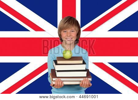 Happy Boy Holding Stack Of Books With Apple Against British Flag