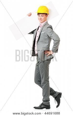 Smiling young businessman in suit and hard hat showing blank placard board, isolated on white background