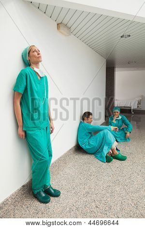 Three surgeons taking break in hospital corridor