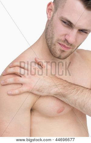 Close-up of shirtless man with shoulder pain over white background