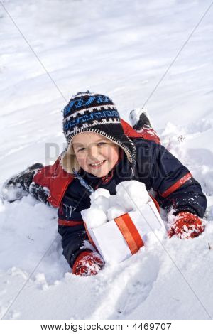 Happy Boy In The Snow With Snowballs In A Box