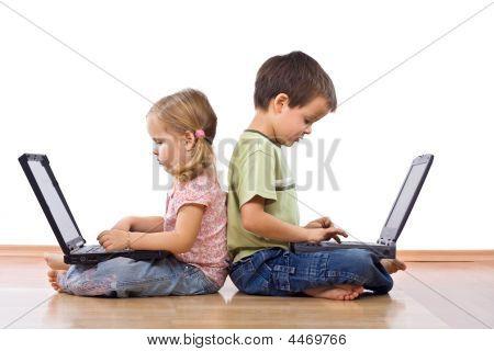 Hermanos utilizando ordenadores portátiles