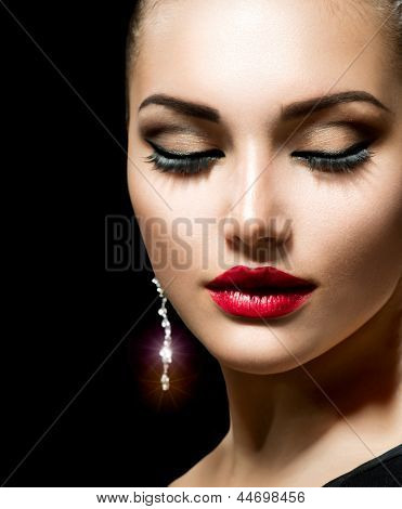 Beauty Woman with Perfect Makeup. Beautiful Professional Holiday Make-up. Red Lips Beauty Girl's Face isolated on Black background. Jewelry