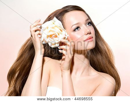 Beauty Girl. Beautiful Model with Rose Flower Touching her Face. Healthy Long Hair and Clear Skin. Youth. Isolated on White Background. Blowing Hair. Skincare concept