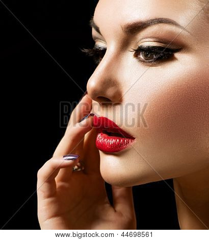 Makeup Face. Beauty Woman with Perfect Make up. Beautiful Professional Holiday Make-up. Red Lips and Nails. Beauty Girl's Face isolated on Black background