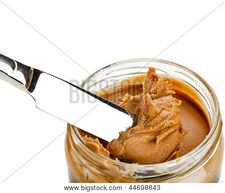 Glass with peanut butter creamy and knife isolated on white background