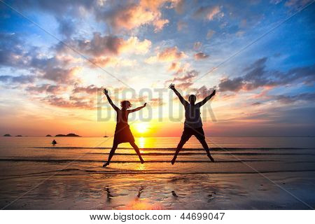 Young couple in a jump on the sea beach at sunset (concept of long-awaited vacation)