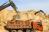 stock photo of backhoe  - Excavator Loading Dumper Truck at Construction Site - JPG