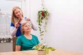 pic of hair comb  - a blond young woman combing seniors hair - JPG