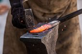 stock photo of anvil  - Detail shot of metal being worked at a blacksmith forge - JPG