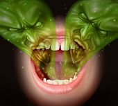 image of vomit  - Bad breath as garlic smell eminating from inside a human mouth as a health concept of an offensive foul odour caused by smoking or eating with a green gas shaped as evil faces over an open human mouth - JPG