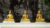 stock photo of metal sculpture  - Buddha on stone babkground in cave of Thailand - JPG