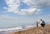 stock photo of walking away  - portrait of father and son on pebble beach - JPG