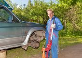 The man in working overalls replaces a wheel at an off-road car