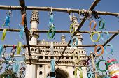 stock photo of charminar  - View looking through a market stall selling bangles towards the landmark Charminar tower in Hyderabad - JPG
