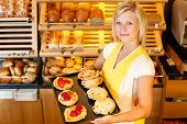 foto of confectioners  - Bakery shopkeeper present different types of cake or pastry - JPG