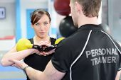 stock photo of kettling  - Young woman working out with kettle bell weights with personal trainer in gym - JPG