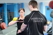 pic of kettling  - Young woman working out with kettle bell weights with personal trainer in gym - JPG