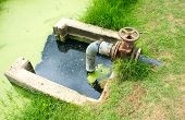 stock photo of sewage  - Waste water draining with valve and concrete pit - JPG