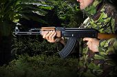 Soldier with rifle AK-47 in jungle