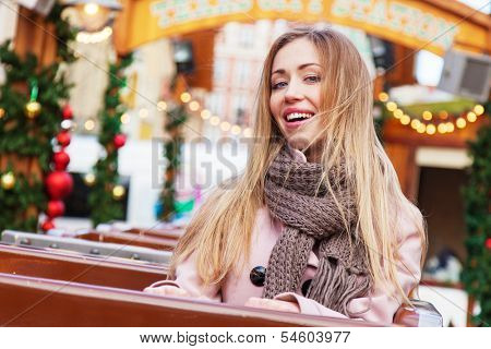 Beautiful young woman on a Christmas rollercoaster
