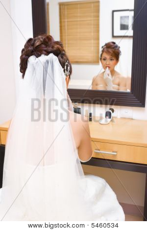 Bride To Be Applying Make Up In Bedroom