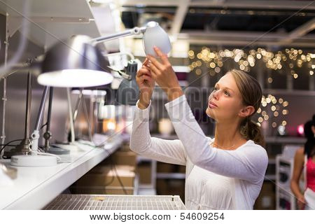 Pretty, young woman choosing the right lamp for her apartment in a modern home furnishings store (color toned image; shallow DOF)