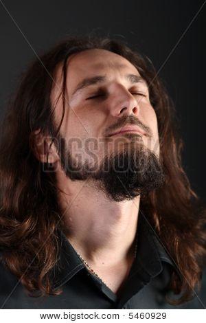 Retrato de un hombre atrapado en medio de la oración sincera con los ojos cerrados