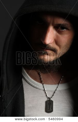 Upset Young Man In Black Hood Looking Left On Black Background