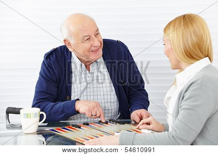Woman playing backgammon with senior citizen in a retirement home