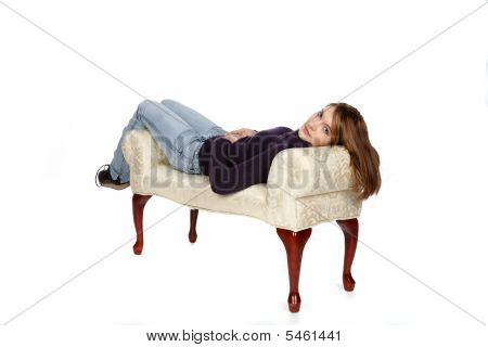 Pretty Teenage Girl Reclining On A White Bench